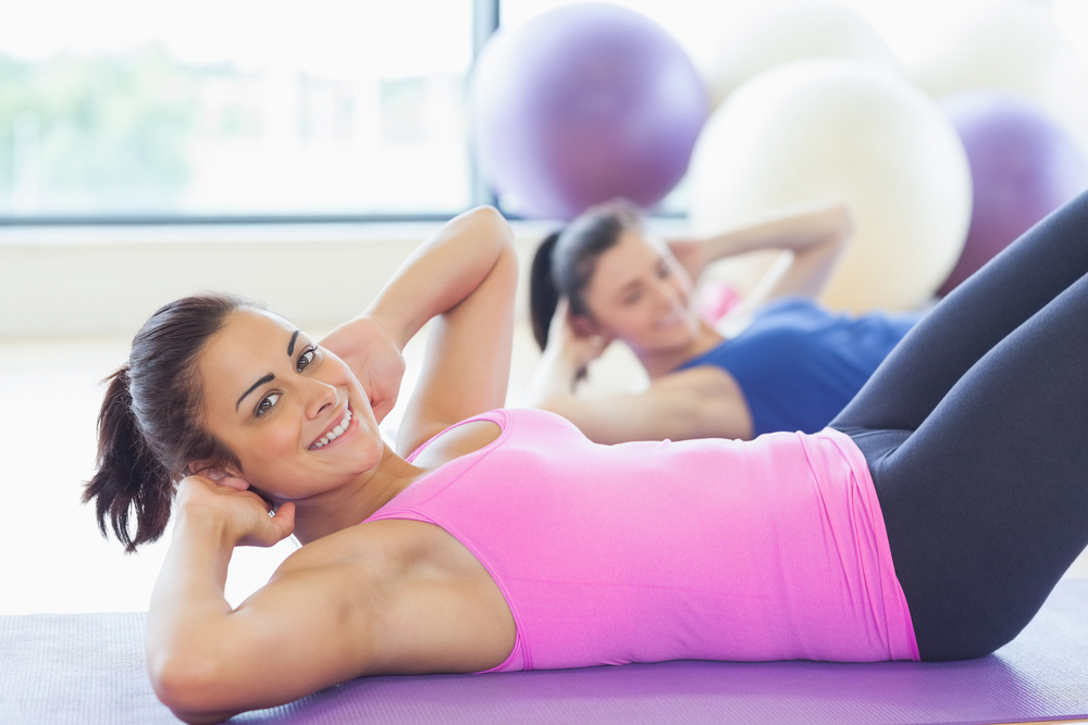 Two fit young women doing pilate exercises in fitness studio
